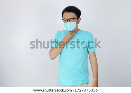 Young Asian man having sore throat and touching his neck with wearing medical mask.  #1727075356
