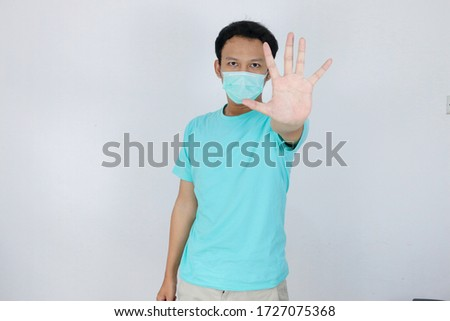 Young asian man wear hygienic mask is scared or panicking with gesturing stop hand. Afraid of coronavirus infection or respiratory illnesses such as flu. Indonesian man isolated on white background #1727075368
