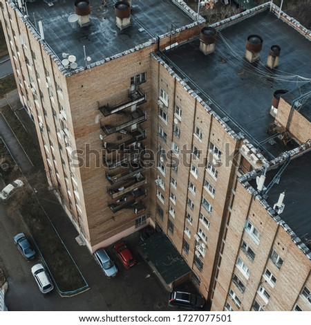 Krasnogorsk, Russia - April 30, 2020: a nine-story brick residential building of Soviet architecture. Metal stairs outside on the facade of the house. The view from the top #1727077501