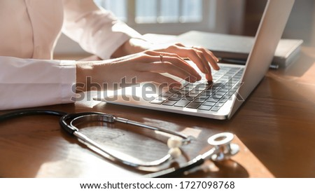 Close up of woman doctor in white medical uniform sit at desk in hospital typing texting consulting client online on laptop, female GP busy working on modern computer gadget in private clinic or lab #1727098768