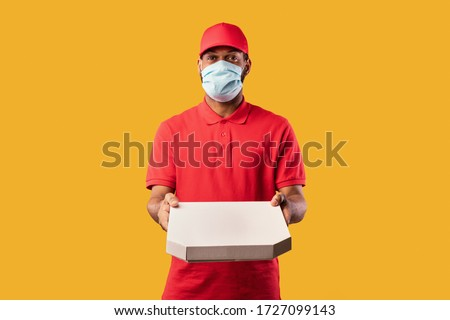 Pizza Delivery. Black Courier Guy Holding Pizza Box Offering It To Camera Wearing Mask Standing On Yellow Background. Studio Shot #1727099143