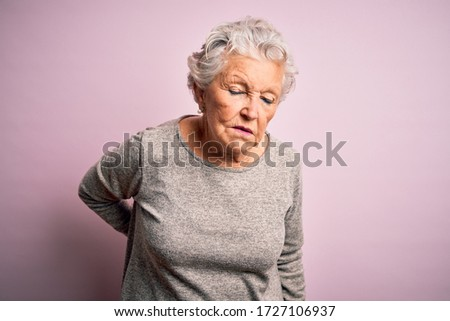 Senior beautiful woman wearing casual t-shirt standing over isolated pink background Suffering of backache, touching back with hand, muscular pain