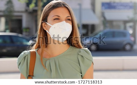 COVID-19 Pandemic Coronavirus Woman in city street wearing KN95 FFP2 mask protective for spreading of disease virus SARS-CoV-2. Girl with protective mask on face against Coronavirus Disease 2019. #1727118313