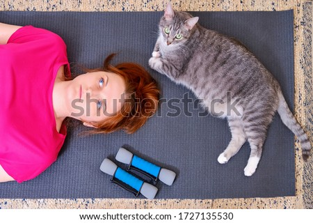 A tired woman and a cat lie on a training mat after a sports workout. Concept of isolation during the coronavirus epidemic and sports training