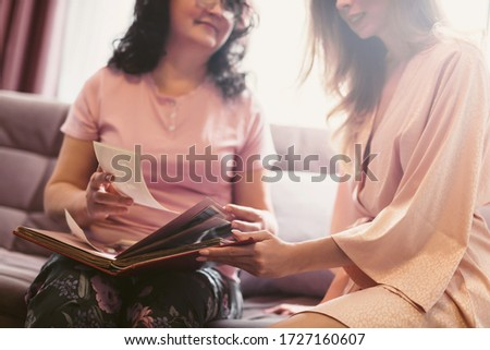 Mother and daughter are watching a family photo album or old film pictures. Weekend with parents, family day, thanksgiving, mom's holiday. Self-isolation