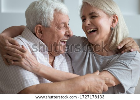 Overjoyed mature husband and wife relax on couch have fun laughing joking together, happy senior couple rest on sofa ta home, smile enjoy leisure family romantic weekend at home, elderly love concept