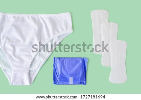 White underpants, few disposable panty liners and regular sanitary pad on a pastel mint background. Flat lay of feminine hygiene items. Top view.