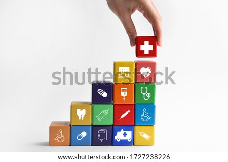 Woman building stairs with colorful cubes on white background. Health insurance concept