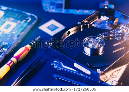 The abstract image of inside of hard disk drive on the technician's desk and a computer motherboard as a component. the concept of data, hardware, and information technology.