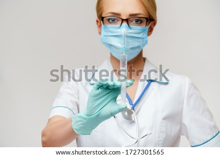 medical doctor nurse woman wearing protective mask and gloves - holding syringe #1727301565