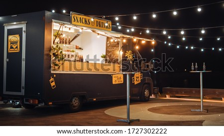 Empty Scene with a Dark Street Food Van Standing in the Evening in a Nice Warmly Lit Neighbourhood Next to the Sea. Food Truck Has Burgers and Drinks for Sale. Tables Have Bottles on Them. Royalty-Free Stock Photo #1727302222