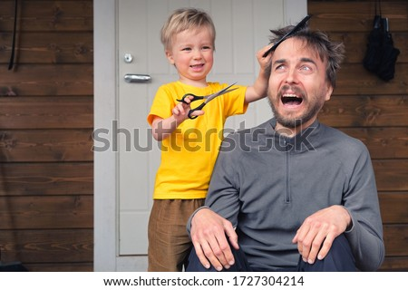 Funny child cutting hair to his father at home during quarantine lockdown. Little hairdresser barber makes haircut to his scared bearded dad. Beauty and selfcare at home lifestyle concept. Royalty-Free Stock Photo #1727304214