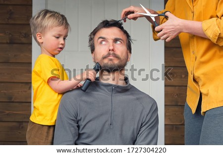 Family haircut at home during quarantine lockdown when closed all hairdressers. Mother cutting hair to father and little child boy cut dad beard with clipper. Beauty and selfcare at home lifestyle. Royalty-Free Stock Photo #1727304220