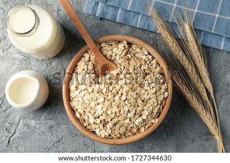Composition with oatmeal flakes on gray background. Cooking breakfast #1727344630