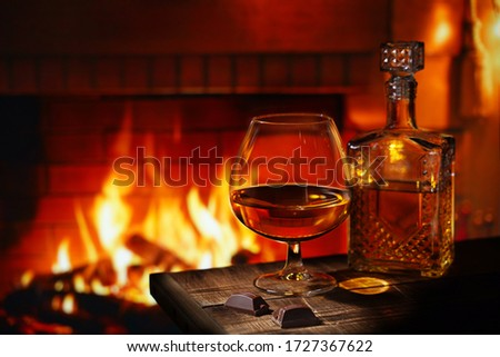 A glass of cognac with a bottle and chocolate on a wooden table near the burning fireplace. Concept winter evening,  heat in the house, holiday. Free space for text.                                Royalty-Free Stock Photo #1727367622