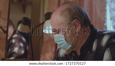 Lonely senior man wore in medical mask has flu symptoms and bad well-being in home.  #1727370127