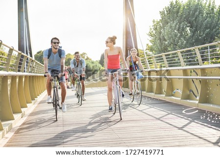 Worker friends going with bicycles on  city park - Young people having fun after work - Eco transport, friendship and healthy lifestyle concept - Focus on center girl face  #1727419771