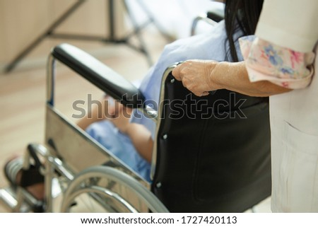 Doctor take care woman patient sit on the wheelchair. Hand take wheelchair to foward. #1727420113
