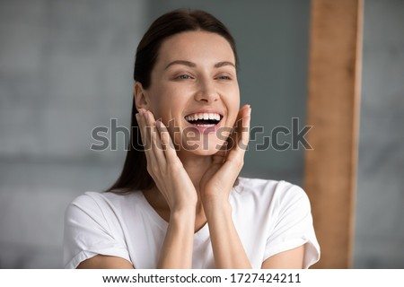 Head shot 35s woman look in mirror touch face enjoy fresh smooth perfect skin after spa anti wrinkle ageing procedure mask moisturizing cream, beauty grooming, skincare and pampering, massage concept Royalty-Free Stock Photo #1727424211