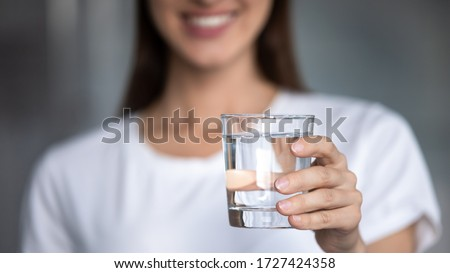 Horizontal banner image, on foreground caucasian female hand holds glass of clear water give to camera smiling selective close up focus. Concept of healthy lifestyle, beauty skin health care treatment Royalty-Free Stock Photo #1727424358
