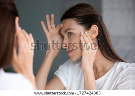 Close up of woman looking in mirror check face after mask cream beauty treatment feels satisfied admire reflection, laser skin resurfacing, glycolic acid peel, anti-ageing skincare procedures concept Royalty-Free Stock Photo #1727424385