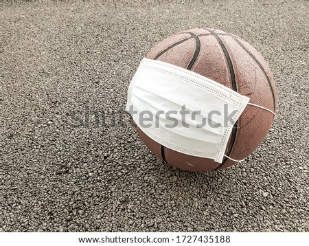Basketball ball wearing surgical medical face mask on ground stone texture background with copy space. Concept for Coronavirus COVID 19 pandemic and epidemic affecting basketball seasons game suspend