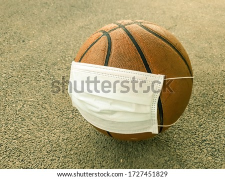 Basketball ball on playground wearing protective medical face mask. Coronavirus COVID 19 Pandemic and epidemic affecting world sport events, game, season, league