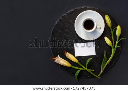 Cup of black coffee and fresh spring buds of lily flowers with clean white business card without massage on a round slate on a black background. Romantic stylish spa breakfast. Space for text flat lay