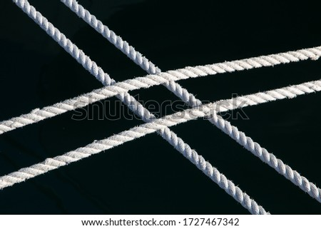 White nautical ropes isolated against black background. Two double marine lines, used to secure a boat, crossed, forming an X letter. Black and white monochrome image.