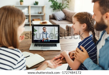 High angle of modern parents and cheerful daughter sitting at table and speaking with online doctor at home #1727484172