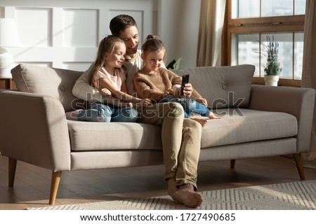 Smiling father with two little daughters using phone, looking at screen, watching cartoons or video, playing game, shopping online, cute preschool girls with dad hugging, sitting on couch at home