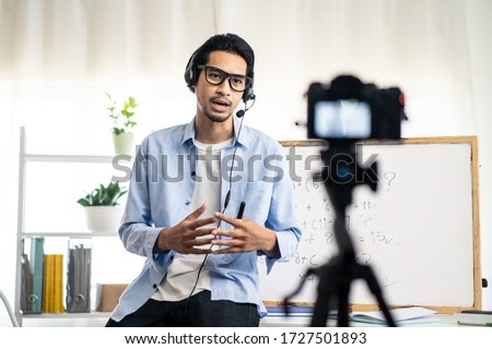 Asian school male teacher working from home teaching online math subject to student studying from home. Man using camera to record his live on internet. Remote education class during covid19 pandemic. Royalty-Free Stock Photo #1727501893