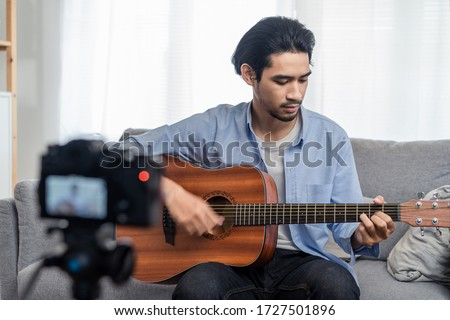 Asian male vlog influencer performancing music and singing show to streaming digital internet online audience listening at home. Man plays guitar and sing a song. Home entertainer and blogger concept. #1727501896