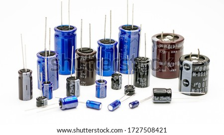 Electrolytic capacitors, many colors and sizes, white background, electronic component concepts #1727508421