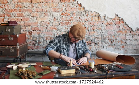Male leather craftsman sews a leather wallet in the workshop. Manufacture of handmade leather products. #1727524462