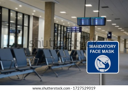 Concept with blue sign warning that face mask is mandatory due to Covid-19 or coronavirus in airport, with a purposely blurred background with an empty airport waiting room #1727529019