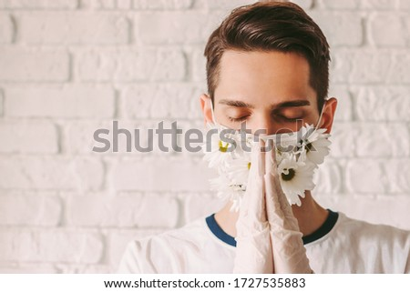 Portrait faithful young man in medical face mask with flowers praying to God for help with coronavirus COVID-19. Religious male doctor in protective gloves and summer face mask with praying hands #1727535883