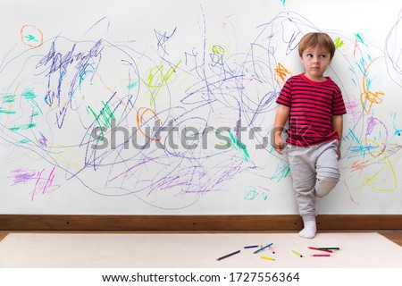 Child mischief. Boy with a distracted face because he drew the entire wall. Little boy leaning against the white wall where he made many drawings with colored pencils. Kid indoors, at home. #1727556364