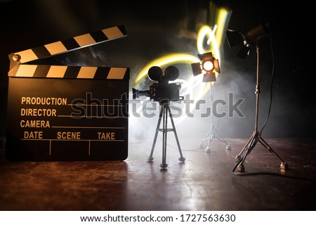Movie concept. Miniature movie set on dark toned background with fog and empty space. Silhouette of vintage camera on tripod and clapboard. Selective focus Royalty-Free Stock Photo #1727563630