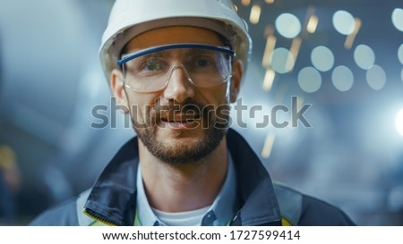 Portrait of Professional Heavy Industry Engineer / Worker Wearing Safety Uniform, Goggles and Hard Hat Smiling. In the Background Unfocused Large Industrial Factory where Welding Sparks Flying Royalty-Free Stock Photo #1727599414