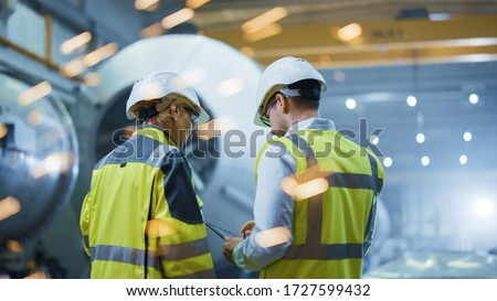 Two Heavy Industry Engineers Stand in Pipe Manufacturing Factory, Use Digital Tablet Computer, Have Discussion. Construction of Oil, Gas and Fuels Transport Pipeline. Back View Sparks Flying #1727599432
