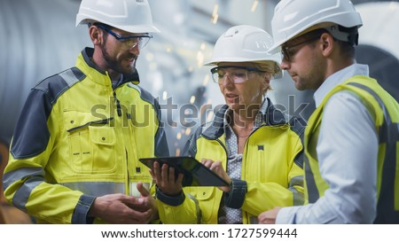 Three Heavy Industry Engineers Stand in Pipe Manufacturing Factory, Use Digital Tablet Computer, Have Discussion. Large Pipe Assembled. Design and Construction of Oil, Gas and Fuels Transport Pipeline #1727599444