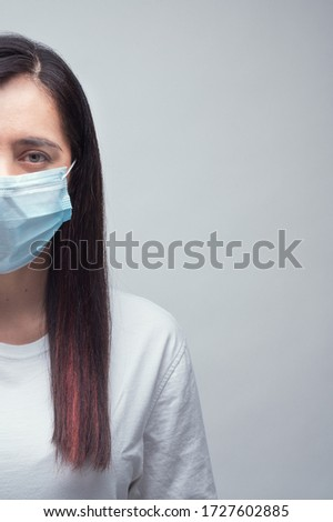Woman portrait in serious mood with face mask, physycal distancing.  #1727602885