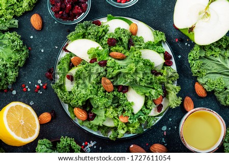 Kale salad with dried cranberry, green apples and almonds. Healthy vegan food, top view, black kitchen table background #1727611054