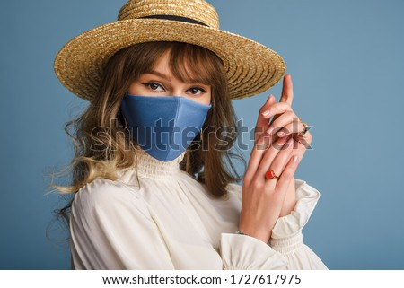 Woman wearing trendy spring, summer fashion outfit during quarantine of coronavirus outbreak. Model dressed protective stylish handmade face mask, straw hat, white blouse, earrings. Copy, empty space #1727617975