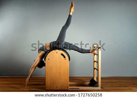 Pilates, fitness, sport, training and people concept - woman doing exercises on a small barrel. Correction of impellent apparatus, correct posture. Royalty-Free Stock Photo #1727650258