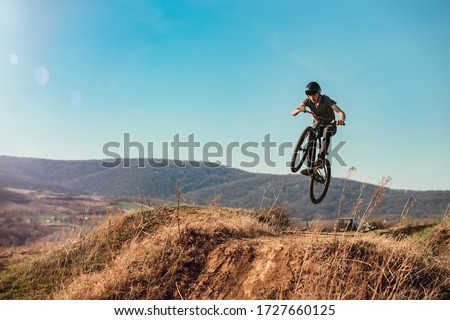 Dirt bike rider jumping in bike park on mountain bike