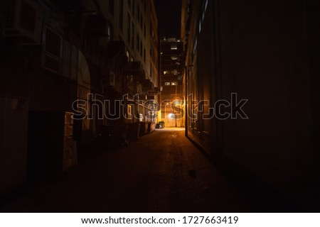 Dark and eerie urban city alley at night Royalty-Free Stock Photo #1727663419