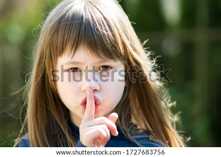Portrait of pretty child girl with gray eyes and long hair holding point finger on her lips with hush sigh. Cute female kid on warm summer day outside. #1727683756
