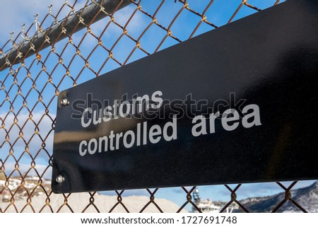 Black sign with white letters spelling customs controlled area. The sign is attached to a mesh wire fence. There is blue sky and clouds in the background. The secure yard restricts a property.